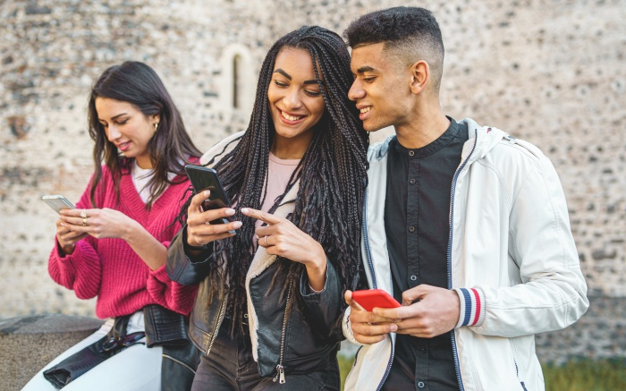 Gen Z young people using smartphone and social networks together. Multiracial people having fun together watching cell phone screens outdoors.