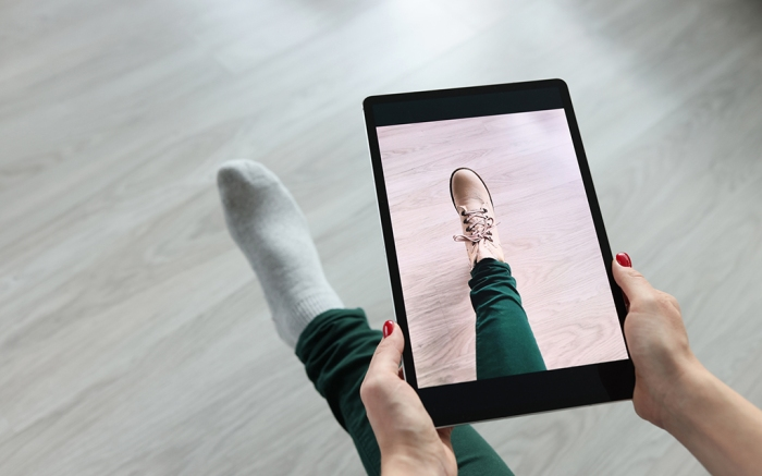 Woman holding tablet over her leg and trying on shoes closeup. Online dressing room concept