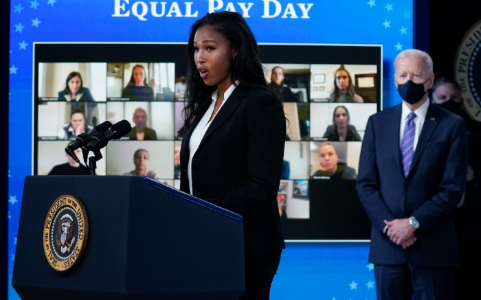 United States Soccer Women's National Team members Margaret Purce speaks as President Joe Biden listens during an event to mark Equal Pay Day in the South Court Auditorium in the Eisenhower Executive Office Building on the White House Campus Wednesday, March 24, 2021, in Washington. (AP Photo/Evan Vucci)