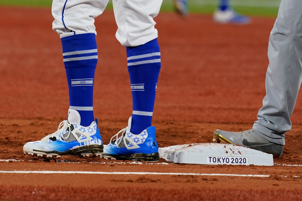 Israel first baseman Danny Valencia, left holds United States' Eric Filia, right, on first base during a baseball game at the 2020 Summer Olympics, Friday, July 30, 2021, in Yokohama, Japan. Valencia's shoes show a pattern of the Star of David. (AP Photo/Sue Ogrocki)