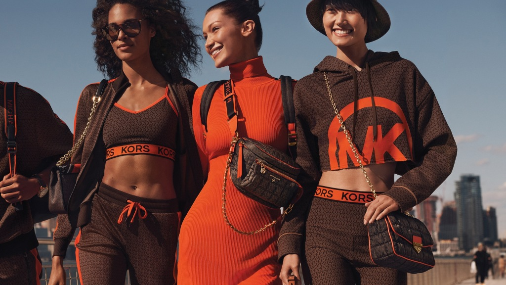 """Bella Hadid is all smiles as she takes a juice break on a fashion shoot. The 24-year-old catwalk beauty stars in the new Michael Kors #MKGO collection. Brand ambassador Bella showcases the fall 2021 look from the US fashion giant - showing off loungewear and athletic-styled designs. She appears alongside models Cindy Bruna and Ash Foo in the New York City-shot images. They model the """"wear-everywhere line"""" for men and women in orange and chocolate brown tones. The collection features joggers, t-shirts, leggings, and knit dresses as well as bags with logo prints and trainers and boots, as well as watches, hats, and sunglasses. """"Equal parts luxe and laid-back, #MKGO offers must-have styles for the ultimate jetsetter, providing exactly the wardrobe refresh that's needed as the world begins to open up again,"""" the brand said in a statement. The line is available now from MichaelKors.com Credit - Courtesy of Michael Kors / MEGA. 18 Aug 2021 Pictured: Bella Hadid for Michael Kors MKGO campaign. Photo credit: Courtesy of Michael Kors/MEGA TheMegaAgency.com +1 888 505 6342 (Mega Agency TagID: MEGA779438_007.jpg) [Photo via Mega Agency]"""