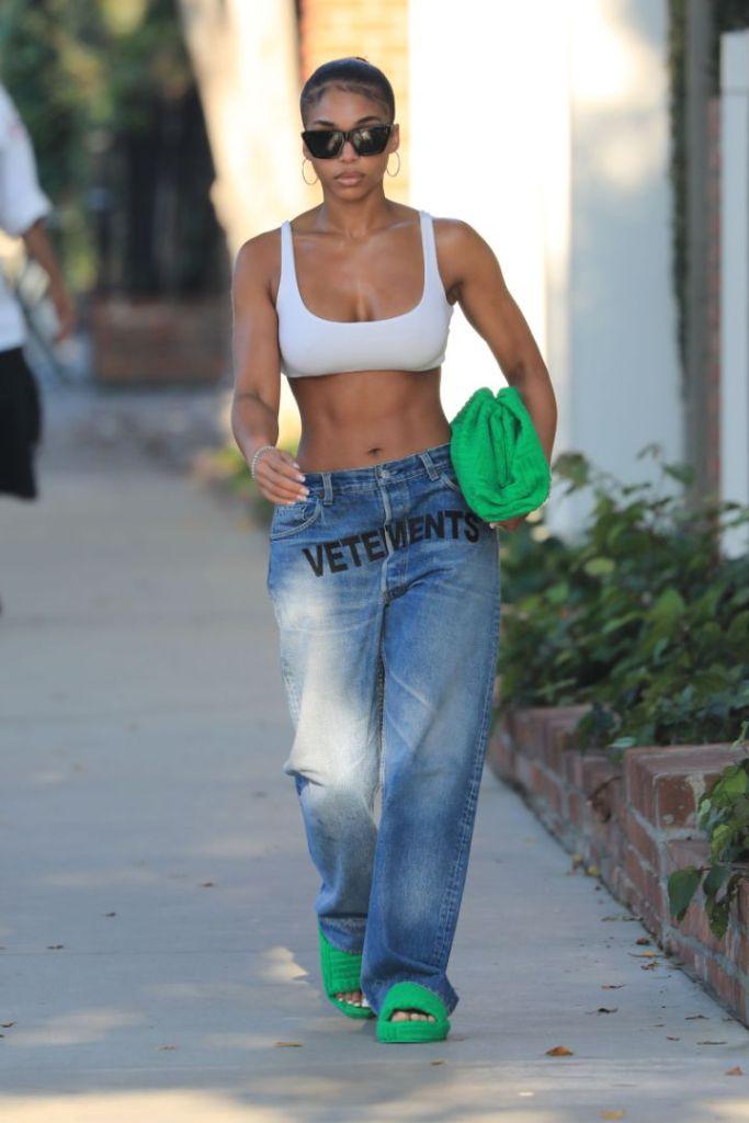 lori harvey, sports bra, bralette, jeans, low-rise jeans, vetemnts, bottega veneta, purse, green sandals, slides, la