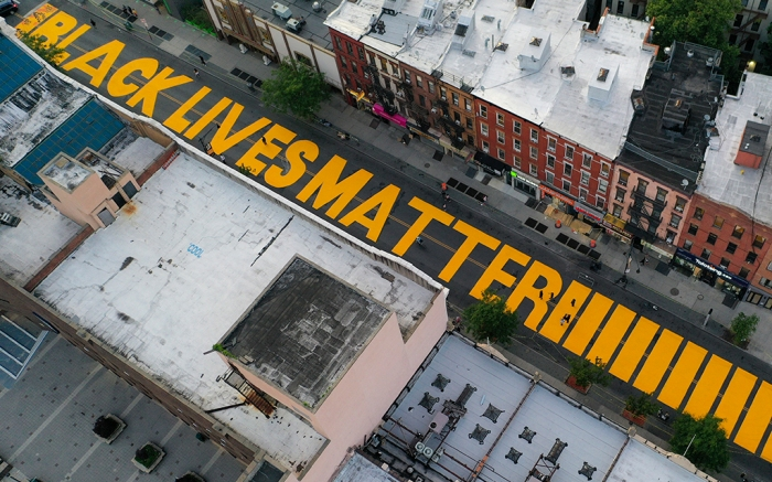 """FILE - In this June 15, 2020, file photo, a sign reading """"Black Lives Matter,"""" is painted in orange on Fulton Street in the Brooklyn borough of New York. On Thursday, June 25, 2020, President Donald Trump used Twitter to voice his displeasure with New York City Mayor Bill de Blasio's plan to paint """"Black Lives Matter"""" in front of Trump's namesake Manhattan tower. (AP Photo/John Minchillo, File)"""