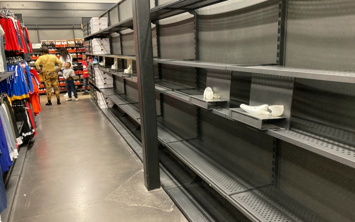 Shelves usually stocked with boxes of shoes sit empty because of supply chain shortages in a Nike outlet store in a mall Tuesday, Oct. 5, 2021, in Castle Rock, Colo